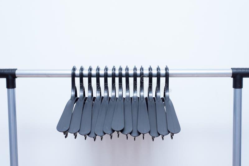 Les cintres en plastique noirs accrochent sur un fond clair beaucoup de différents cintres Support de manteau de plancher photographie stock