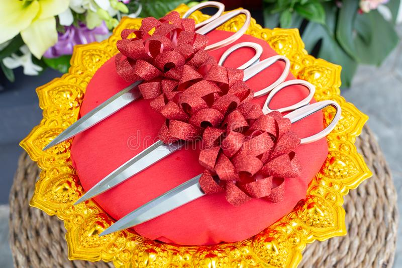Les ciseaux en acier avec le satin rouge de ruban cintrent sur le plateau d'or à grand photographie stock libre de droits