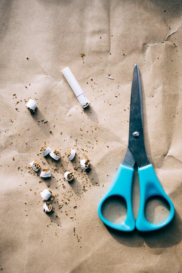 Les ciseaux ont coupé une cigarette, lumière dure, monde aucun jour de tabac images stock