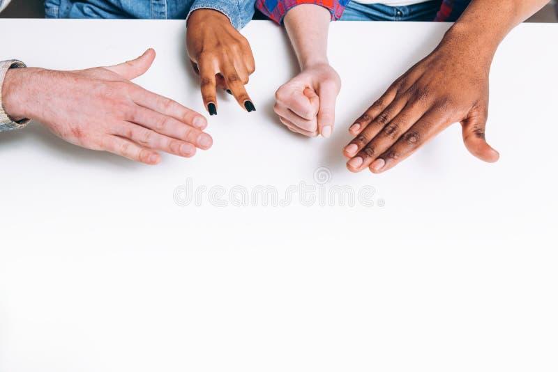 Les ciseaux papier de roche de jeu, quatre mains jouent Amusement images stock