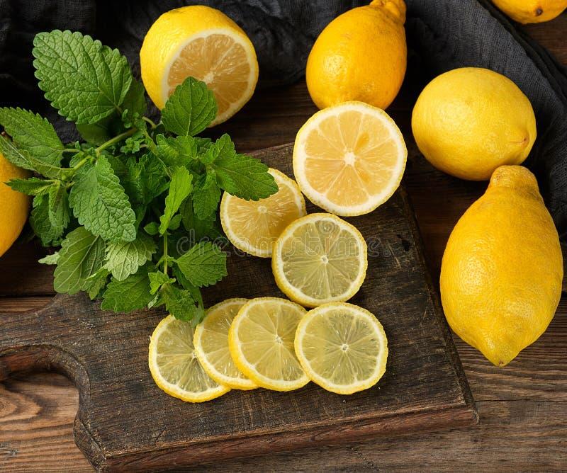les citrons jaunes coupés en tranches sur un conseil en bois brun, à côté de lui se trouve un groupe de menthe verte photo libre de droits