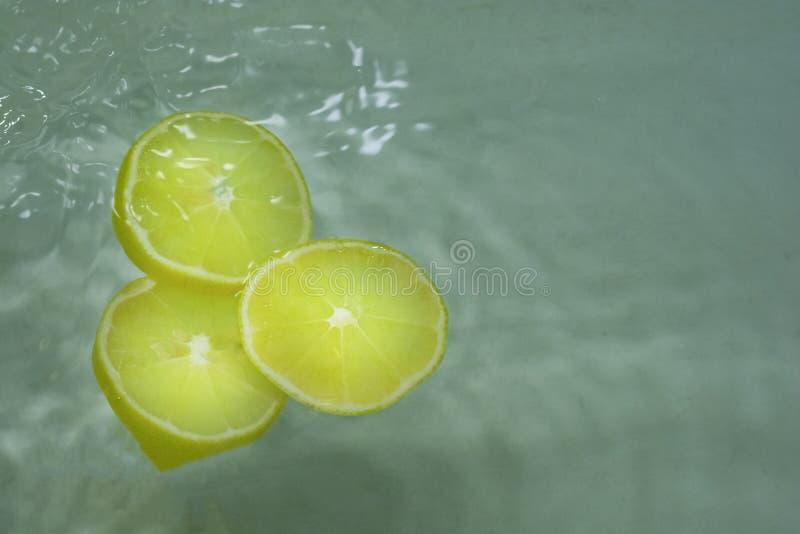 Les citrons jaunes lumineux partagent des citrons avec de l'eau photos stock