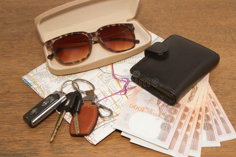 Les clés et les lunettes de soleil sur une carte de route avec l'argent de poche, préparent au TR image libre de droits