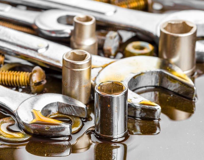 Les clés et les outils de mécanicien ont souillé avec de l'huile de moteur image stock