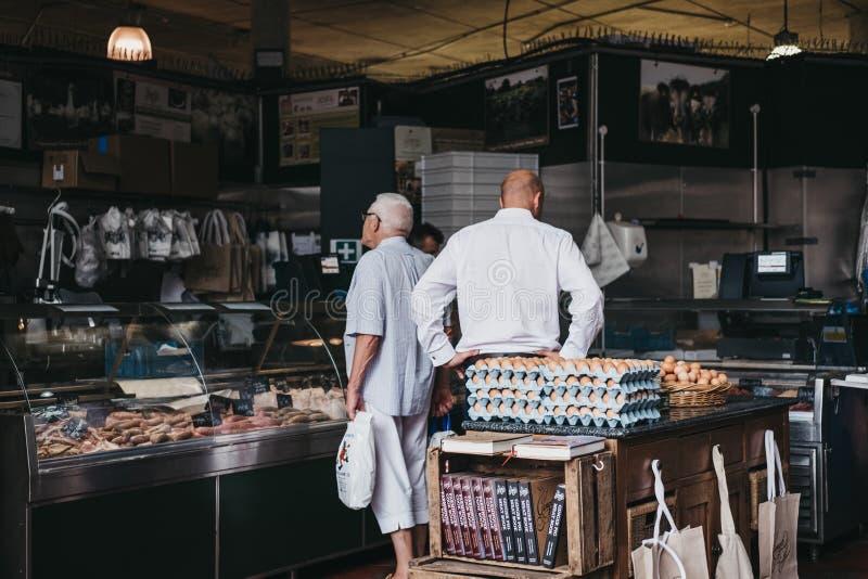 Les clients à l'intérieur d'un ` s de boucher se tiennent au marché de ville, Londres, R-U images libres de droits