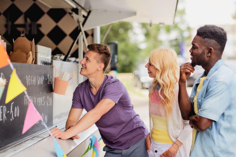 Les clients heureux font la queue ou des amis au camion de nourriture photographie stock libre de droits