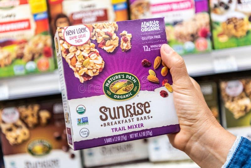 Les clients remettent tenir un paquet des bars de cuisine organiques de lever de soleil de la marque de la nature photographie stock libre de droits