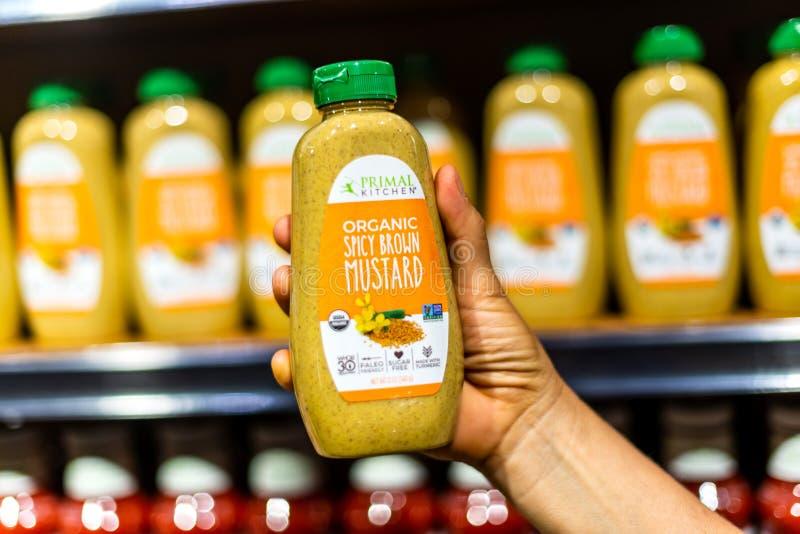 Les clients remettent tenir un pot de moutarde brune épicée organique de marque principale de cuisine photographie stock libre de droits