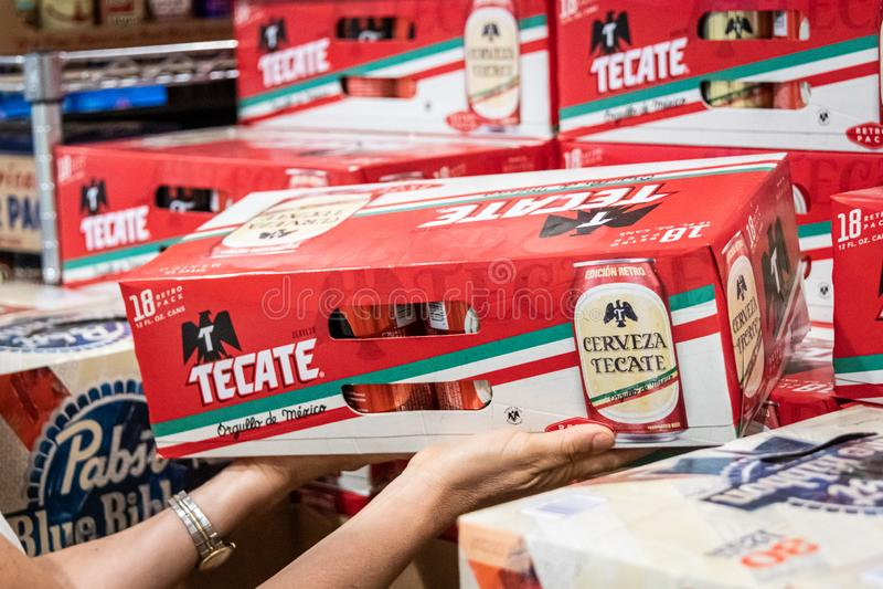 Les clients remettent tenir une boîte de 18 boîtes de bière mexicaine de marque de Tecate photos stock