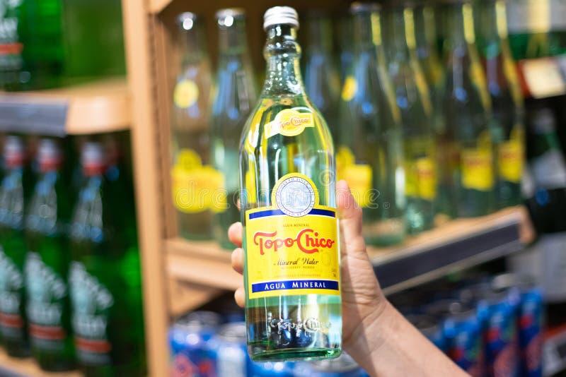 Les clients remettent tenir une bouteille de topo chico image stock
