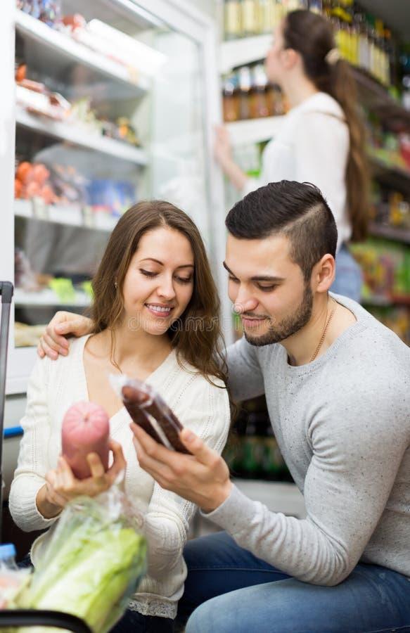 Les clients s'approchent du réfrigérateur avec des produits carnés image libre de droits