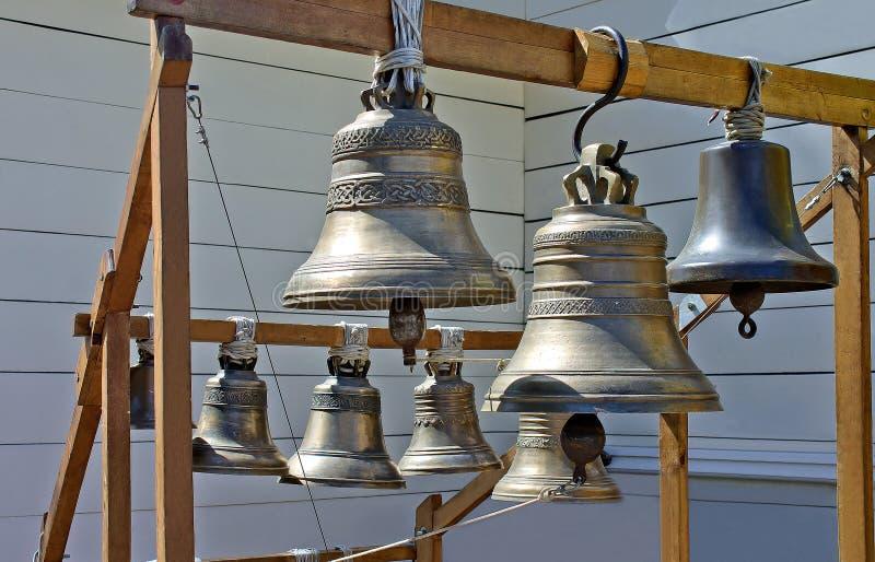 Les cloches d'église accrochent sur les structures en bois, différentes dans la forme et la taille images libres de droits