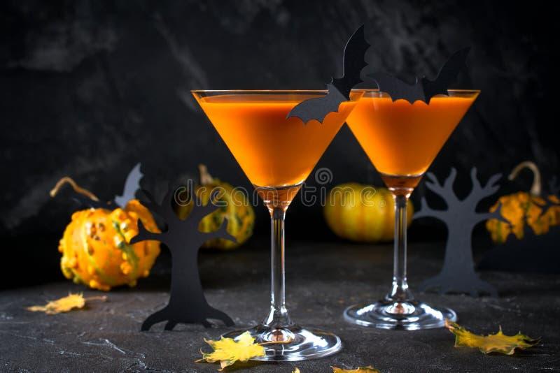 Les cocktails oranges de martini avec des battes et le décor pour Halloween font la fête, sur l'obscurité photo stock