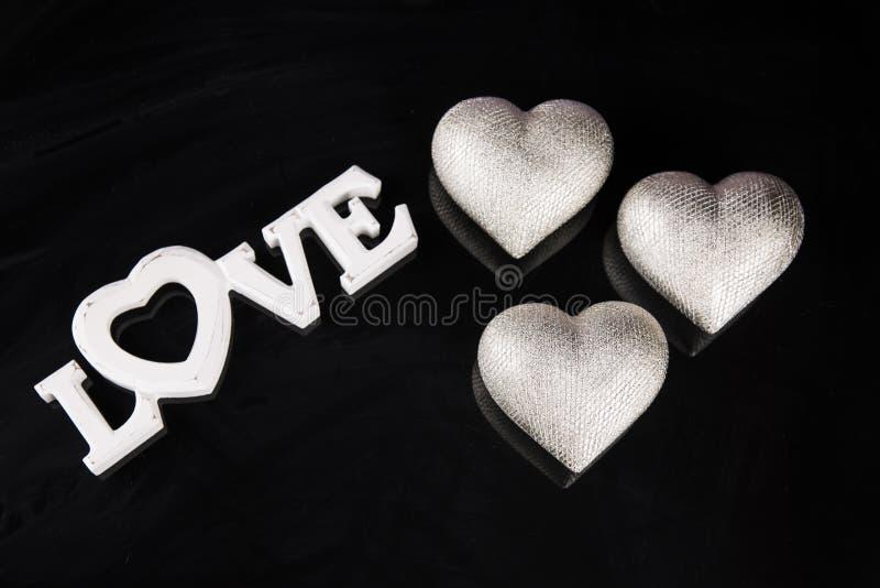 Les coeurs argentés sur un fond noir avec les mots aiment pour le jour de valentine images libres de droits