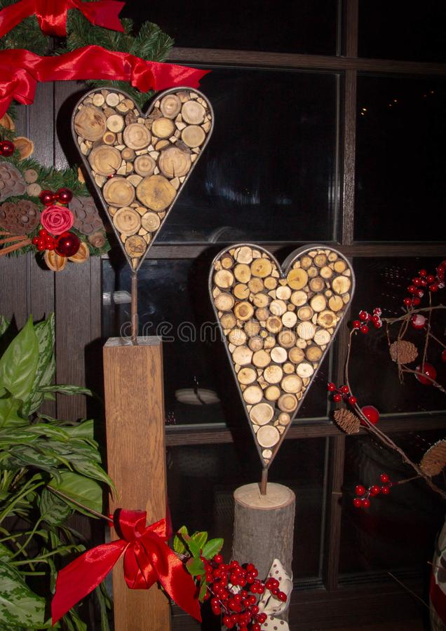 Les coeurs décoratifs du fond deux sonnent les branches de l'arbre entouré par les rubans et le feuillage rouges images stock