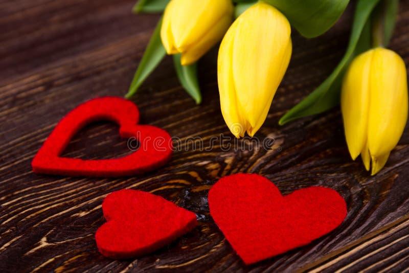 Les coeurs de tissu s'approchent des tulipes photo stock