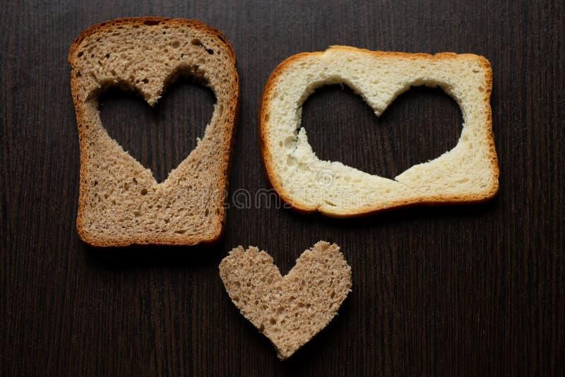 Les coeurs ont découpé d'un morceau de pain sur une table en bois photos libres de droits