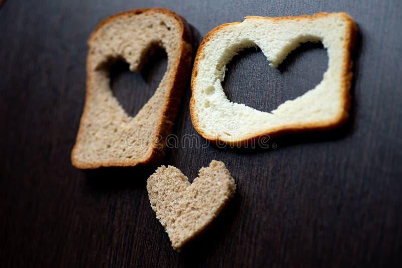Les coeurs ont découpé d'un morceau de pain sur une table en bois photographie stock libre de droits