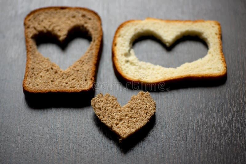Les coeurs ont découpé d'un morceau de pain sur une table en bois images stock