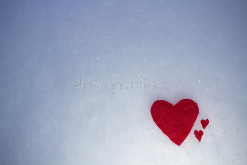 Les coeurs rouges de textile se trouvent sur la neige froide pelucheuse images libres de droits