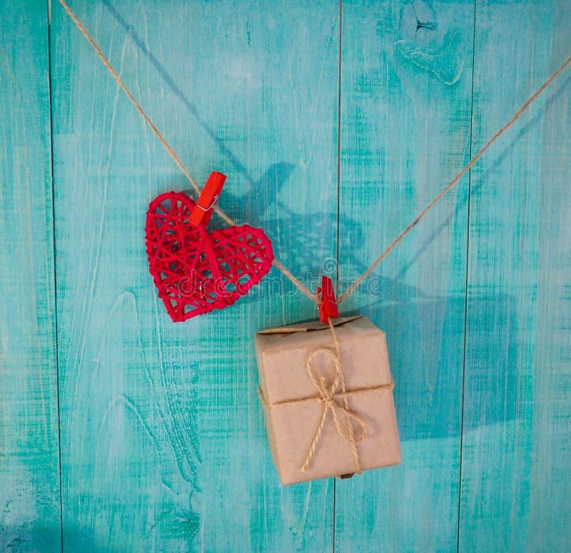 les coeurs rouges de tissu de pays accrochant sur la corde à linge avec le jour de valentines en bois rustique de porte, enfante  photo libre de droits
