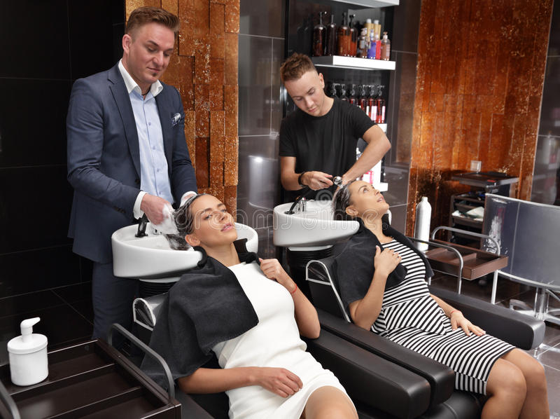 Les coiffeurs de salon de beauté lavent la tête de la fille photos libres de droits