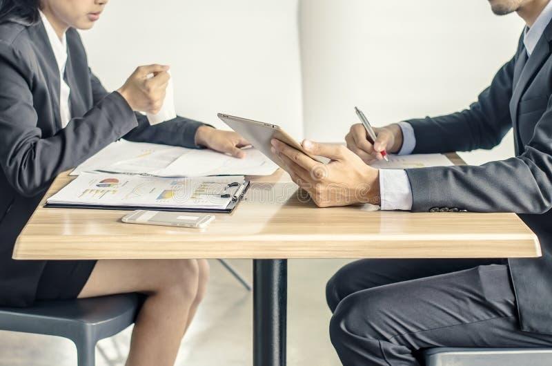 Les collègues d'affaires appréciant une pause-café souriant à quelque chose sur l'écran d'un comprimé se sont tenus par un des ho images stock