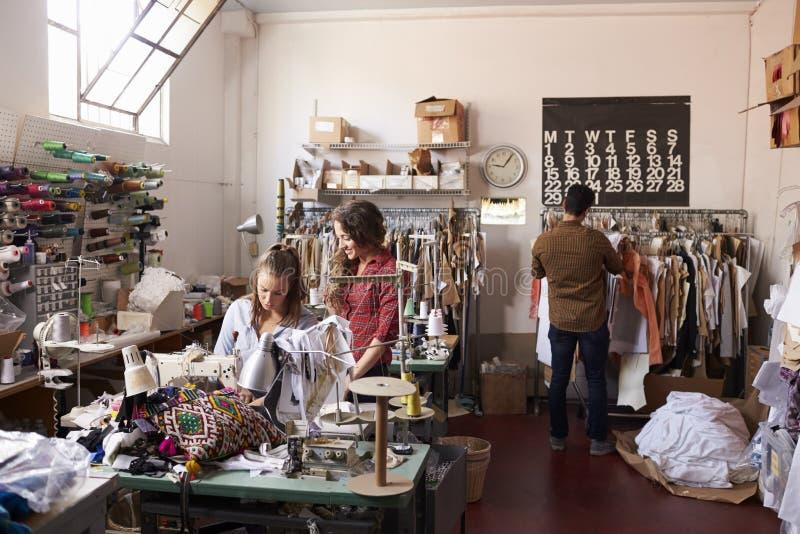 Les collègues travaillant à l'des vêtements conçoivent le studio, intégral photos libres de droits