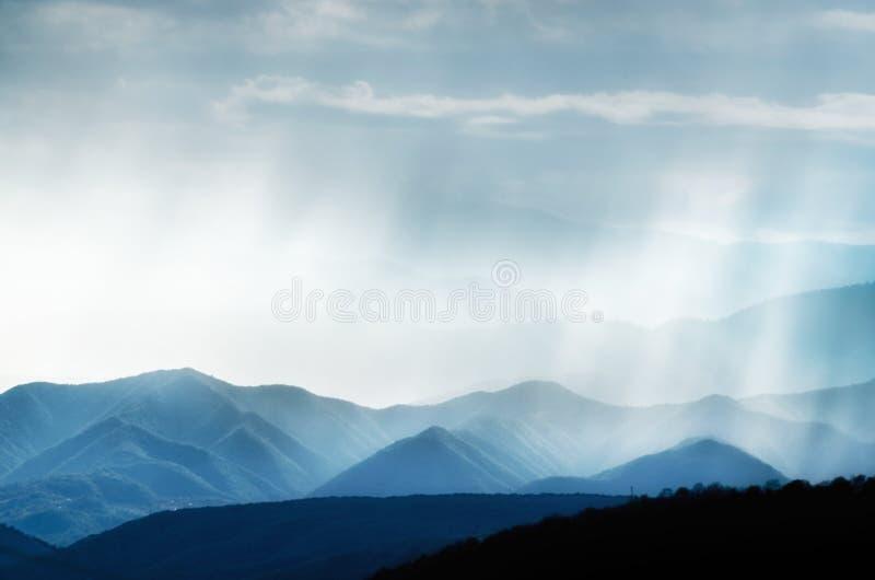 Les collines avec les gammes brumeuses, pluvieuses et fumeuses ont accentué avec la lumière du soleil photographie stock libre de droits
