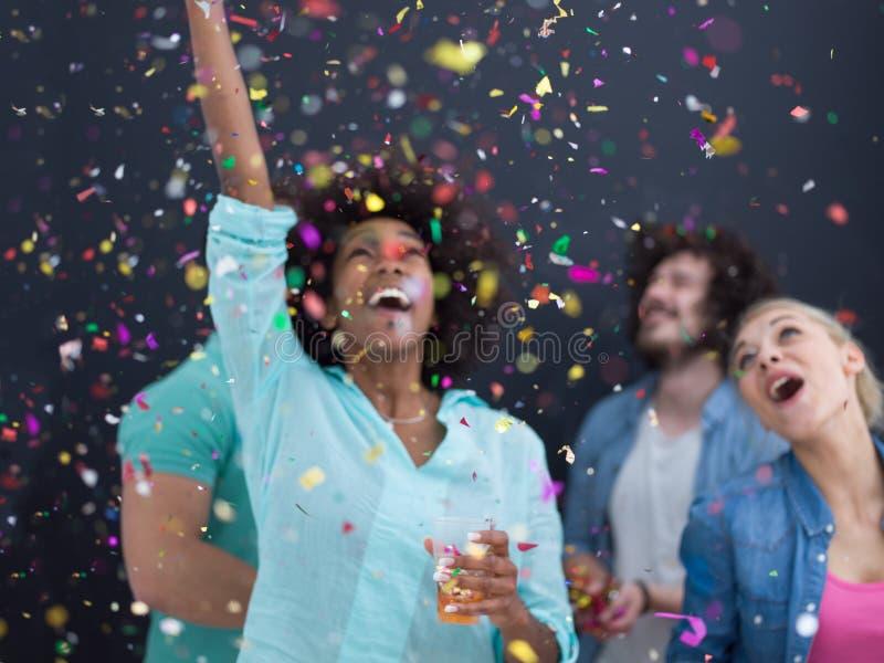 Les confettis font la fête le groupe de personnes multi-ethnique au-dessus de gris photographie stock libre de droits