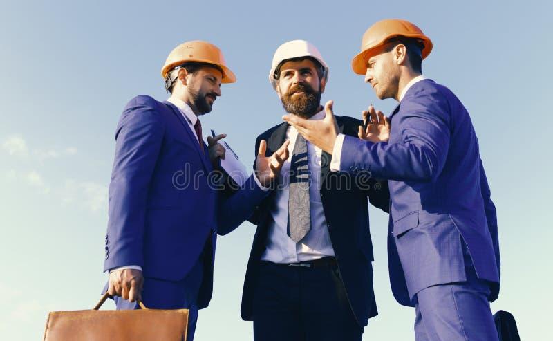 Les constructeurs discutant le plan et discutent, fond de ciel bleu images libres de droits