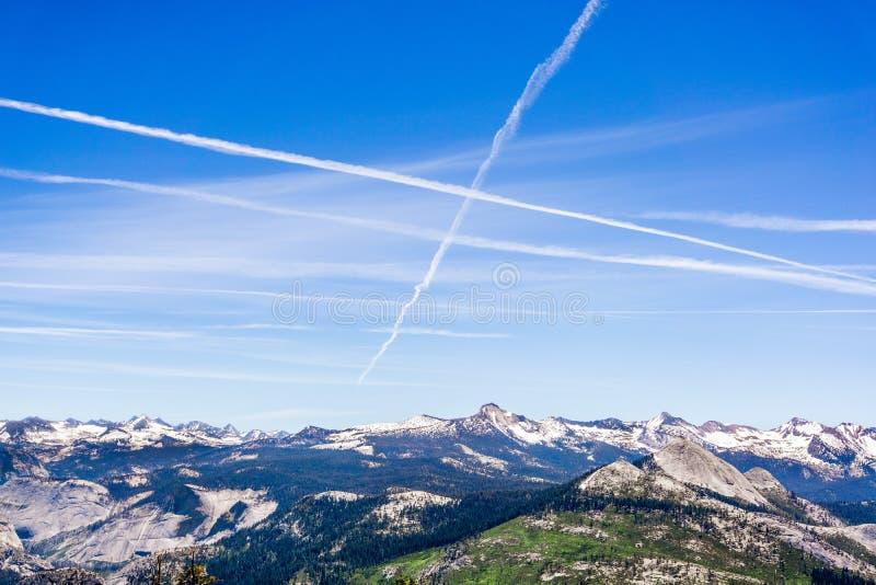 Les contrails multiples croisent des chemins par le ciel bleu au-dessus de la neige ont couvert des montagnes ; Parc national de  images libres de droits