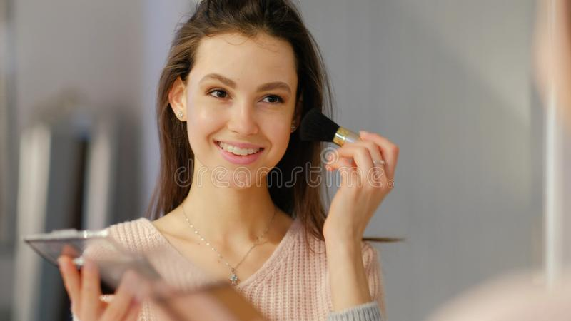 Les cosmétiques de maquillage de beauté que la fille de mode de vie s'appliquent rougissent images libres de droits