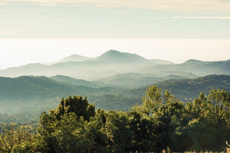 Les couches de la montagne parmi la brume et le soleil s'allument image stock