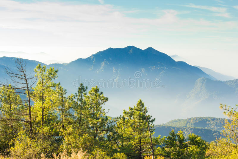 Les couches de la montagne parmi la brume et le soleil s'allument image libre de droits