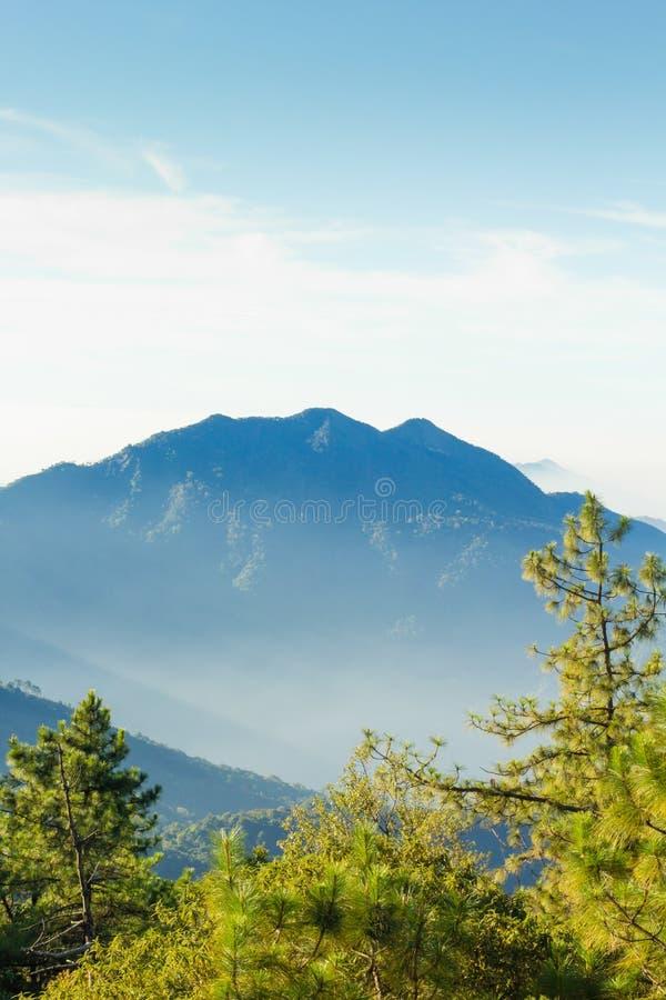 Les couches de la montagne parmi la brume et le soleil s'allument photos libres de droits
