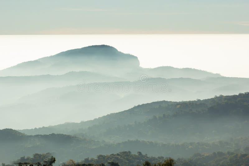 Les couches de la montagne parmi la brume et le soleil s'allument photos stock