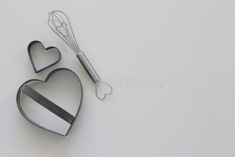 Les coupeurs en forme de coeur de biscuit et battent photos stock