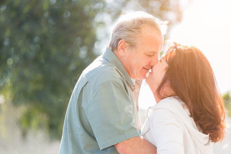 Les couples âgés par milieu apprécient un romantique ralentissent la danse et le baiser dehors images stock