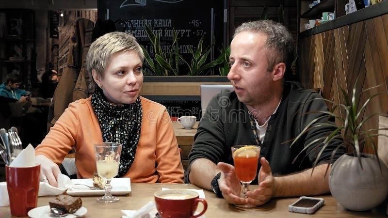 Les couples équipent et la femme mange des entretiens dans le restaurant de café photo stock