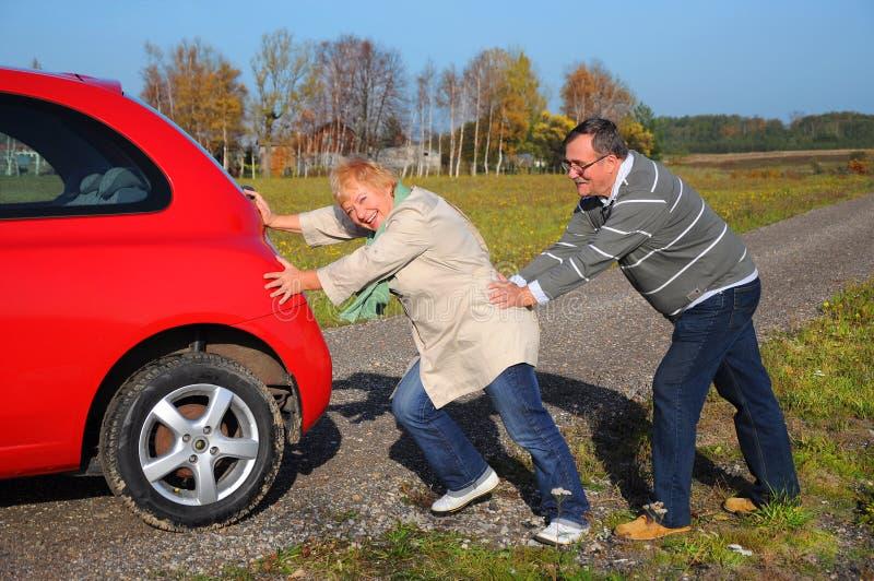 Les couples aînés poussent le véhicule cassé photographie stock