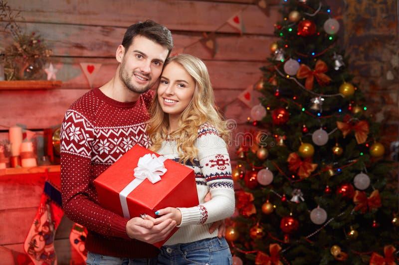 Les couples affectueux élégants gentils s'approchent de l'arbre de Noël photographie stock libre de droits