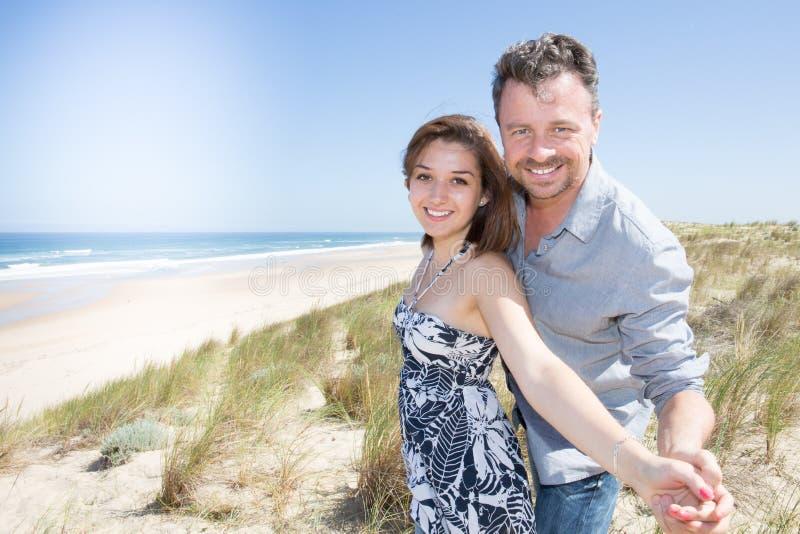 Les couples apprécient des dunes sable et vacances de plage en quelques vacances d'été photo libre de droits