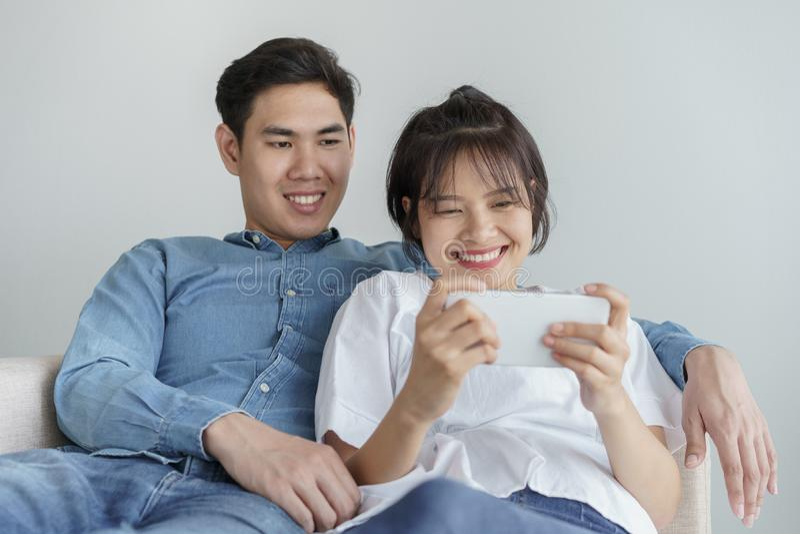 Les couples asiatiques de jeune amour heureux se reposant sur le divan à la maison, regardant le téléphone portable, les couples  photographie stock