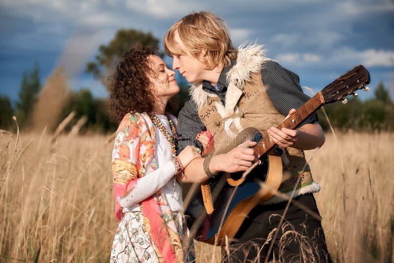 Les couples attrayants de style de Boho dans l'amour posant l'automne mettent en place photo libre de droits