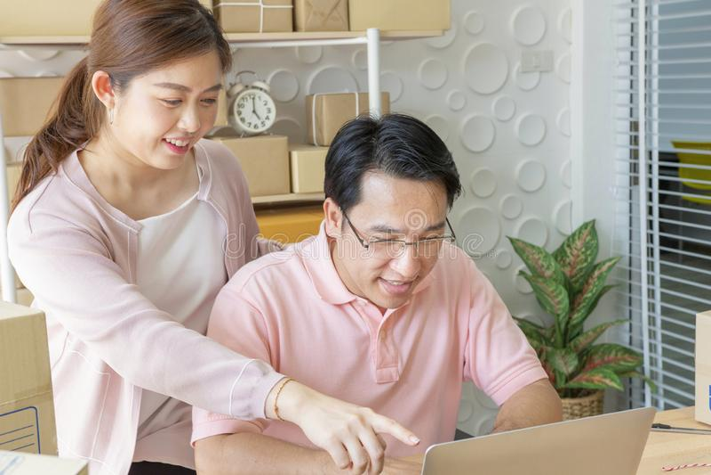 les couples autoguident l'ordinateur portatif utilisant Pointage à l'écran avec heureusement photographie stock libre de droits