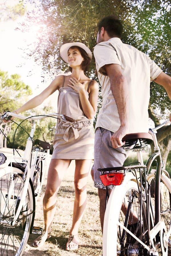 Les couples ayant des bicyclettes montent dans la nature photo libre de droits