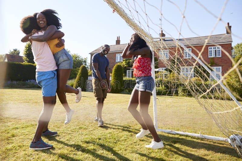 Les couples célèbrent le but de marquage pendant un jeu fun du football photographie stock