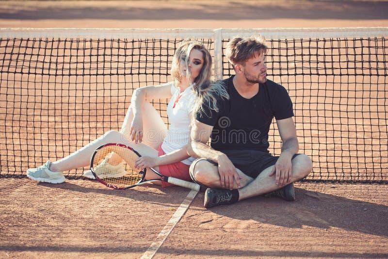 Les couples détendent sur le court de tennis après la formation Le sportif et la sportive s'asseyent au filet Les joueurs de tenn photo libre de droits