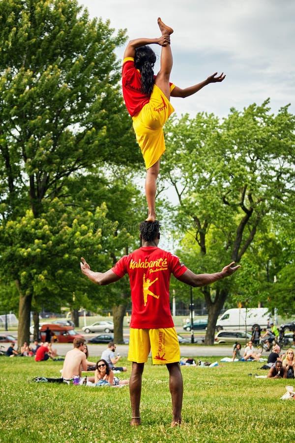 Les couples d'afro-américain exécutant des acrobaties montrent devant l'assistance dans le parc royal de bâti photo stock